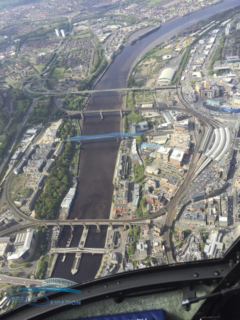 Overhead the Tyne bridges in one of our Robinson R44 helicopters